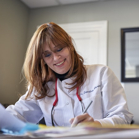 Dr. Morin writing notes about periodontics in Woburn, MA