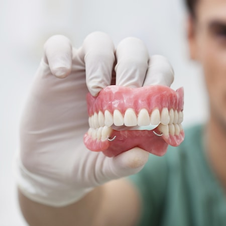 Woburn dentist holding a set of partial dentures