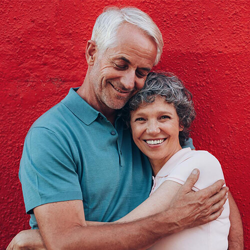 Older couple smiling and hugging after their Woburn dental services, which included an oral cancer screening