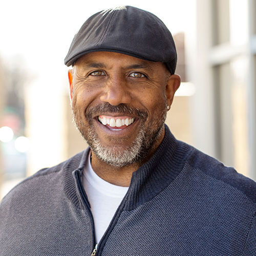 Handsome, smiling, middle-aged man wearing a hat.