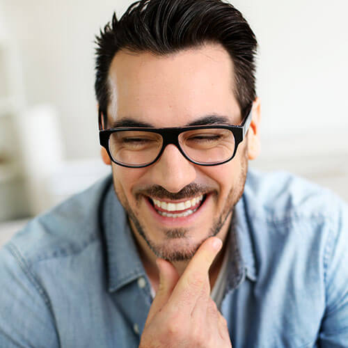 Dark-haired man with glasses laughing with delight over his new smile.