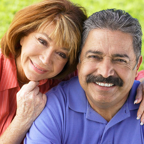 Middle-aged couple smiling into camera.
