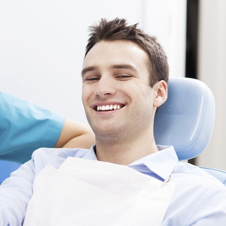 Man smiling after having an extraction of his wisdom teeth