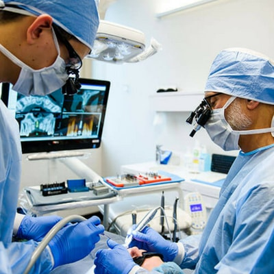 Two Woburn dentists using conventional surgical loupes for low magnification