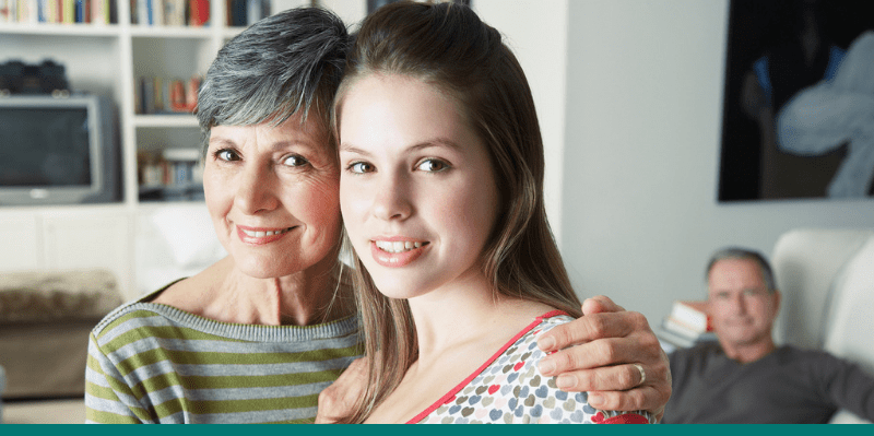 Grandma holding shoulders of teen granddaughter, both smiling to show that you should consult with your dentist regarding age limits on dental implants.