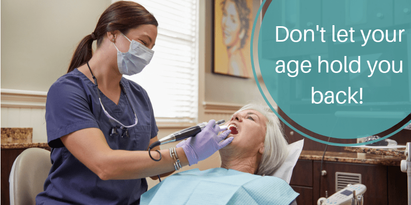 Hygienist examines older woman laying back in a dental chair with the words Don't let your age hold you back from getting dental implants