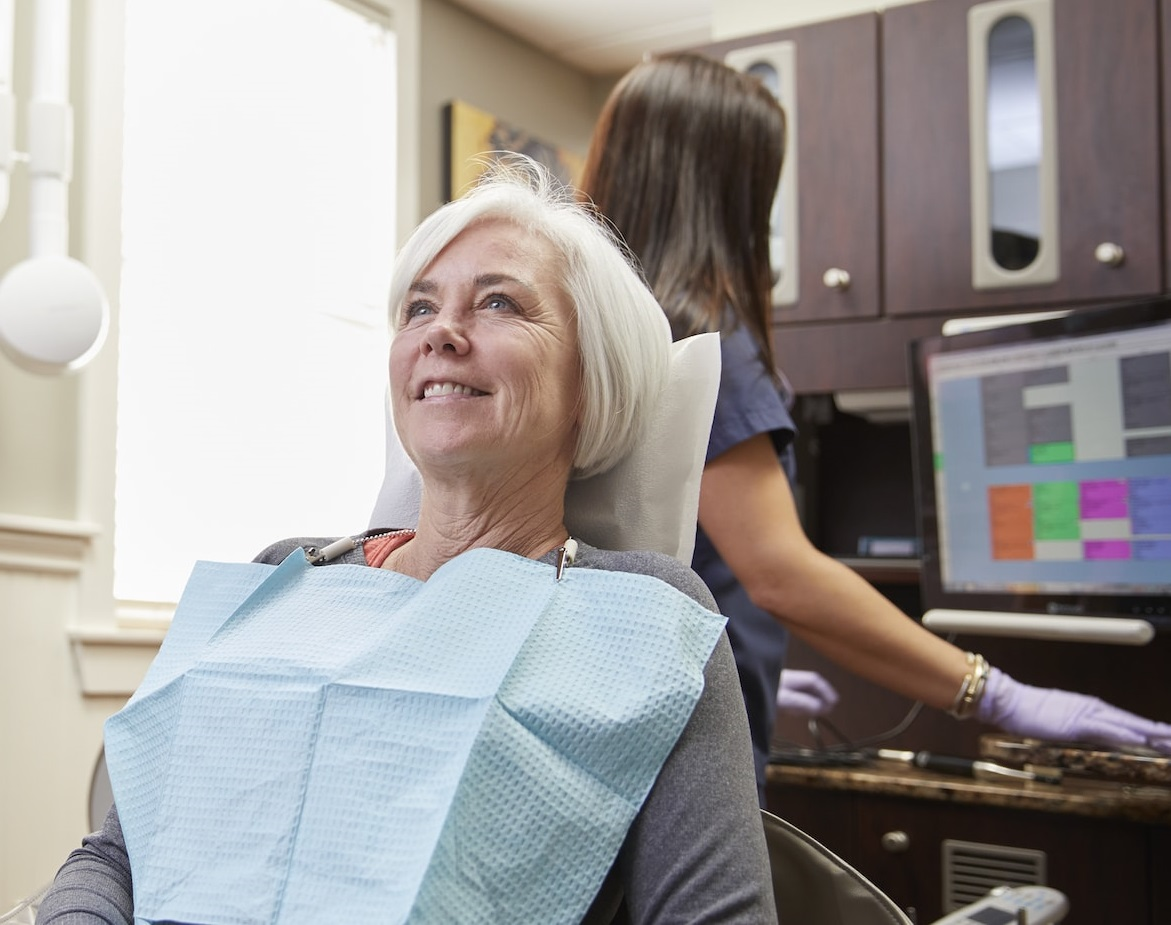 Smiling woman in dental chair for TMJ treatment.