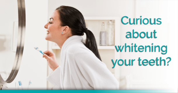 Woman looking at her teeth in a mirror and considering teeth whitening.