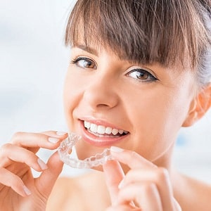 Smiling woman putting Invisalign aligner tray into her mouth.