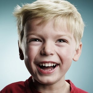 Close-up of a young boy with a big smile on his face.