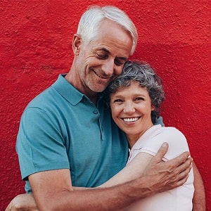 Older man and woman hugging against a red background.