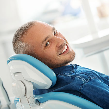 Young man smiling in dental chair preparing for bone grafting procedure.