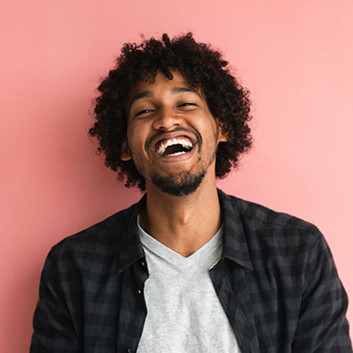 Man smiling against a pink background with healthy teeth from periodontics in Woburn, MA.
