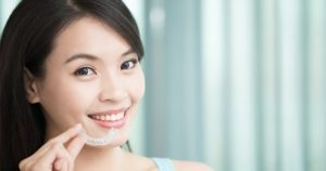 A woman smiling while holding a clear aligners after reading Invisalign FAQs