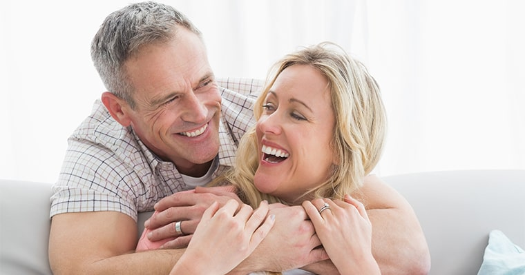 An older couple embracing and smiling after getting dental implants in Woburn, MA